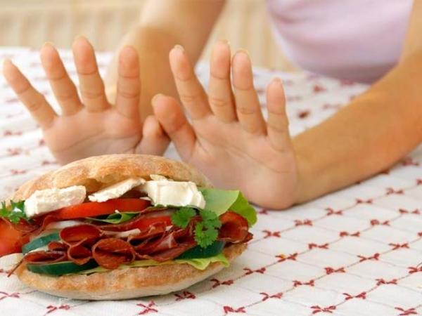 Девушка отодвигает от себя гамбургер