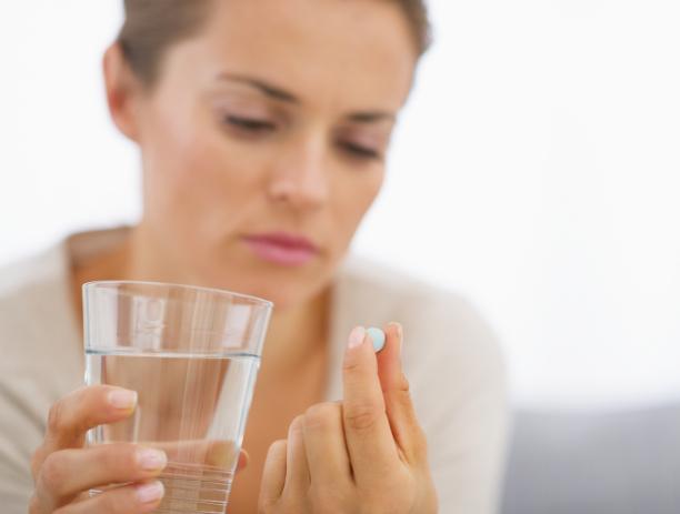 Женщина думает стоит ли пить антибиотик