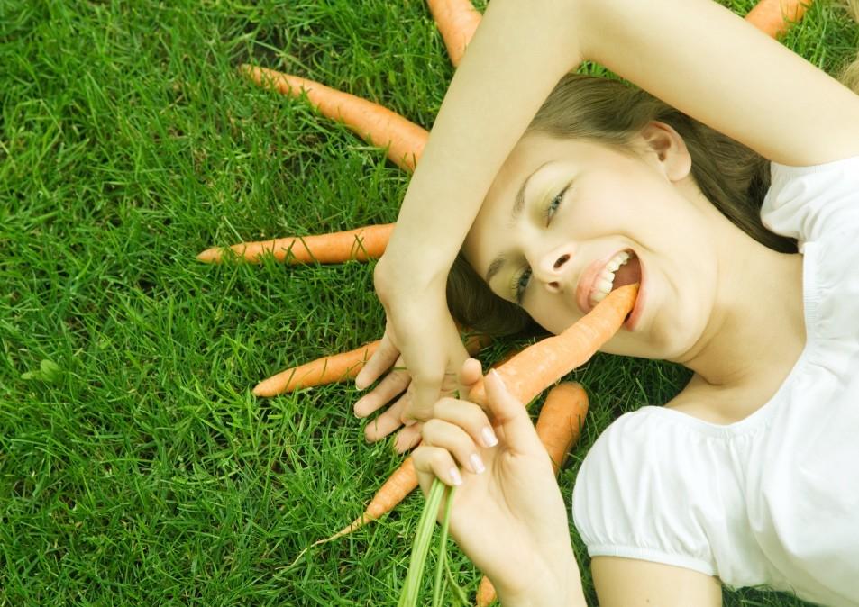 Девушка лежит на траве с морковкой во рту