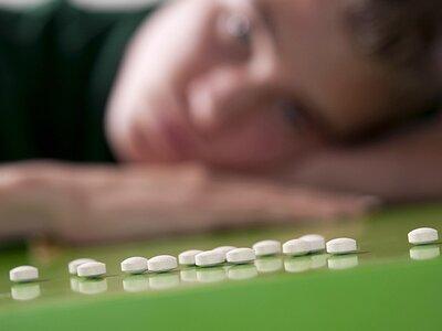 Человек смотрит на лекарства, лежащие на столе