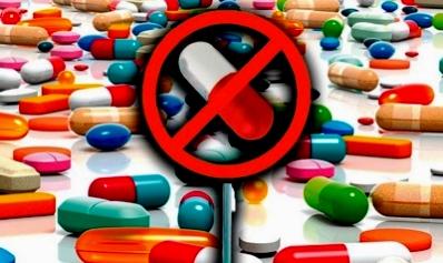 Таблетки и капсулы, рассыпанные по слолу