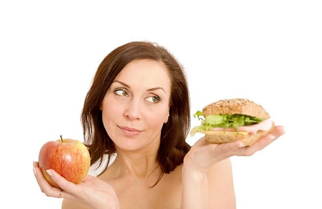 Девушка держит яблоко и гамбургер