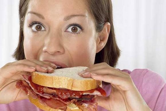 Девушка есть большой бутерброд