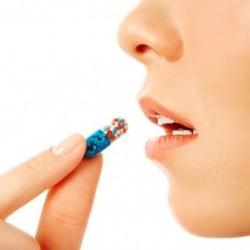Фото: Девушка принимает таблетку